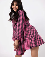 model moves wearing pink and black check alice collared dress while smiling against white background