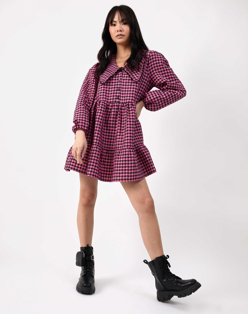 model wearing alice pink and black check dress with collar against white background in black biker boots
