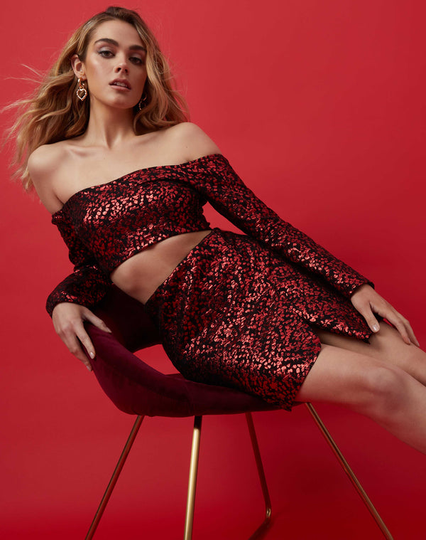 model leans on red velvet arm chair in the kim glitter red mini skirt with slit and matching bardot top in front of a red background