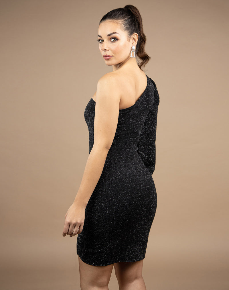 model looks over her shoulder in the jessie one shoulder lurex dress showing the back of the dress