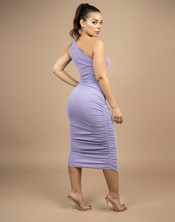 we see the back of the model wearing the Raquel Lilac Ruched Midi Dress with perspex shoes