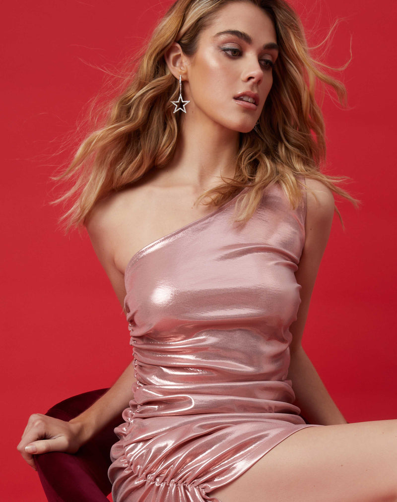 the model's hair blows while sitting on a chair wearing the georgia ruched one shoulder pink high shine dress in front of a red background