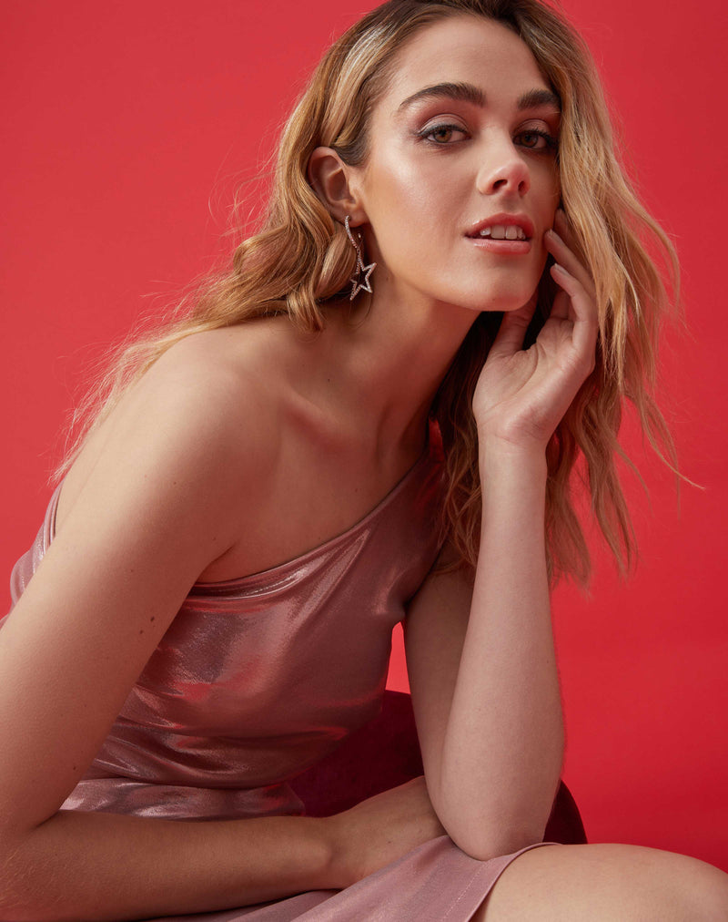 a close up image of the model with her head in her hand smiling while wearing the georgia ruched pink one shoulder dress in pink in front of a red background