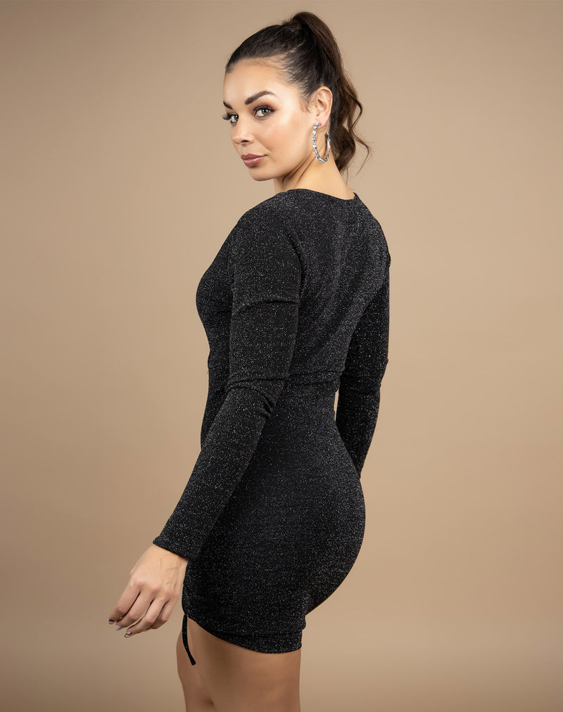 the model looks over her shoulder in the anne lurex wrap ruched dress showing the back of the dress in front of a beige background