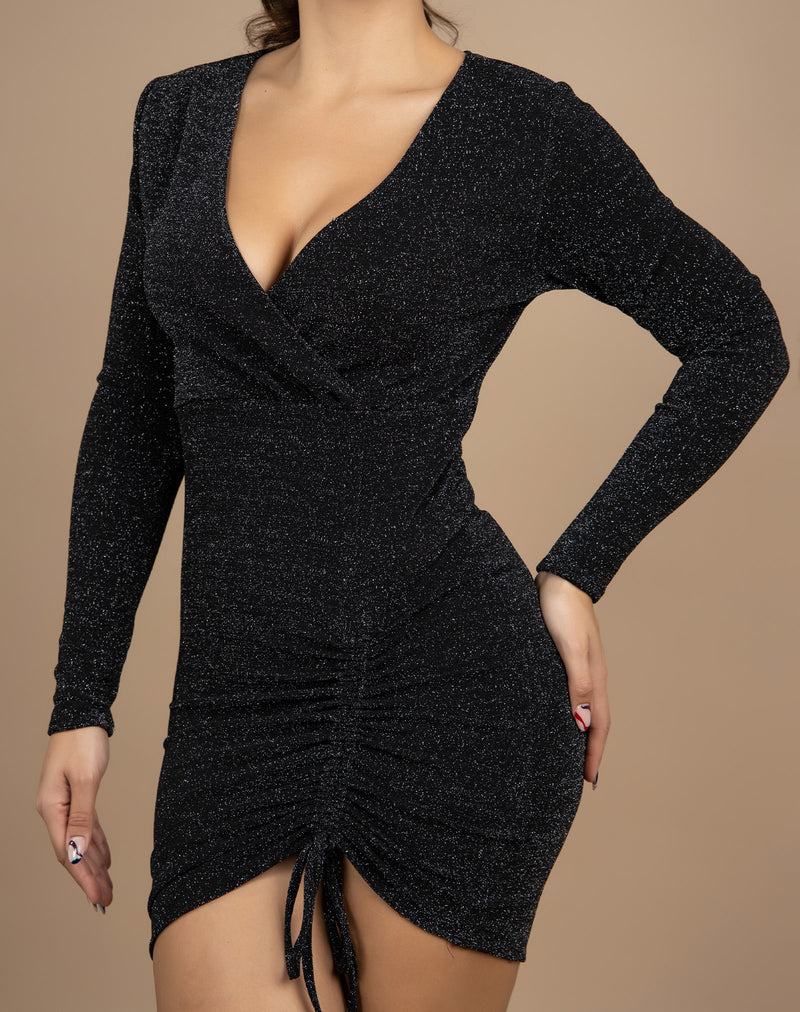 a close cropped image of a model wearing the anne lurex wrap ruched dress with long sleeves with her hand on her hip in front of a beige background