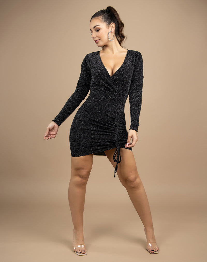 the model leans to one side with her hands in front while wearing the long sleeves anne lurex wrap ruched dress with a v neck in front of a beige background