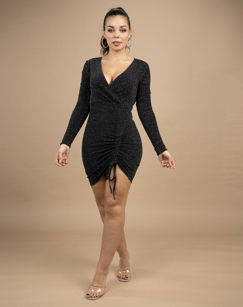 a full length image of the model wearing the anne lurex wrap ruched dress with her arms by her side and ankles crossed in front of a beige background