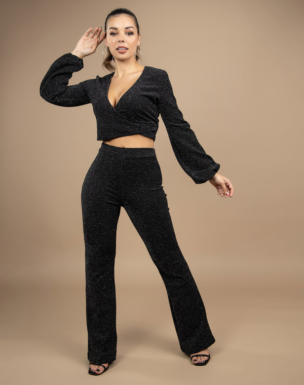 model wears black lurex two piece with wide trousers and wrap long sleeve top in front of a beige backdrop in a studio full length