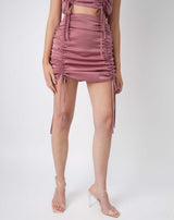a close up shot of the model wearing the Noor Pink Satin Ruched Skirt with perspex heels