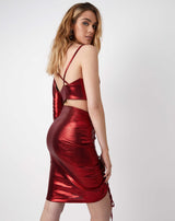 model shows the back of the kourt red ruched shiny skirt with matching top