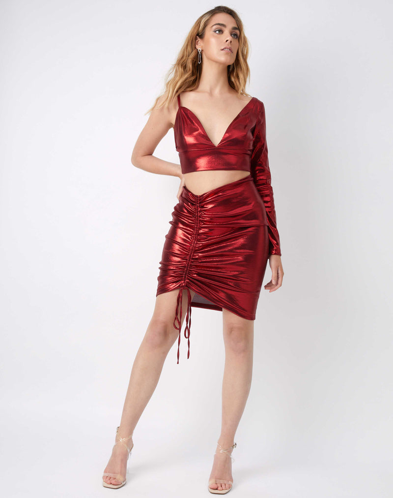 full length image of model with hand on hips wearing the kourt red ruched shiny skirt and matching top