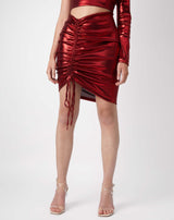 cropped close image of model wearing the kourt red ruched shiny skirt with nude perspex heels