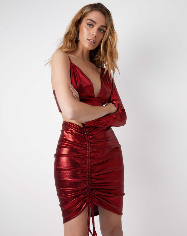 model has arms crossed wearing the kourt red ruched shiny mini skirt with matching top