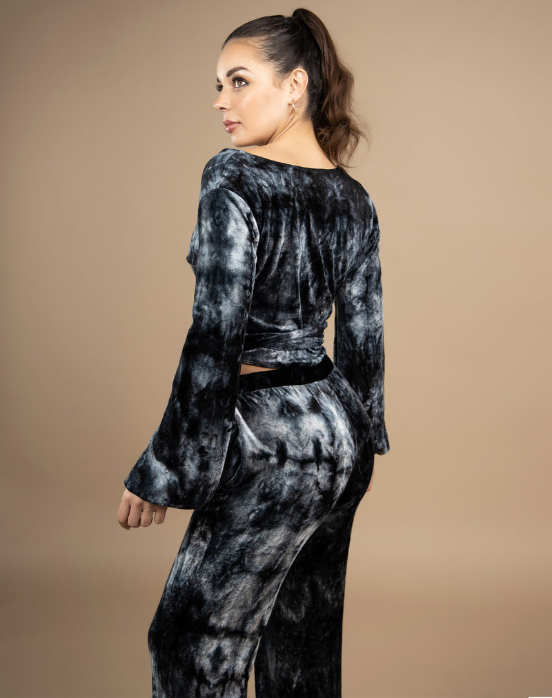 the model faces away from the camera wearing the fran tie dye velour wrap top with long sleeves and matching trousers