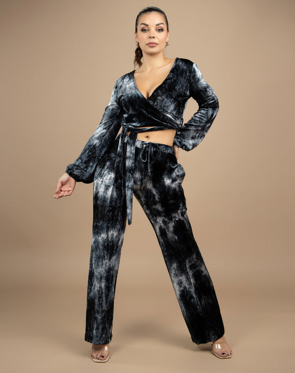 a full length image of the model wearing the fran tie dye velour wrap top with side tie and matching trousers