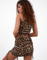 the model wears the dani leopard print ruched front top with the matching skirt facing away from the camera