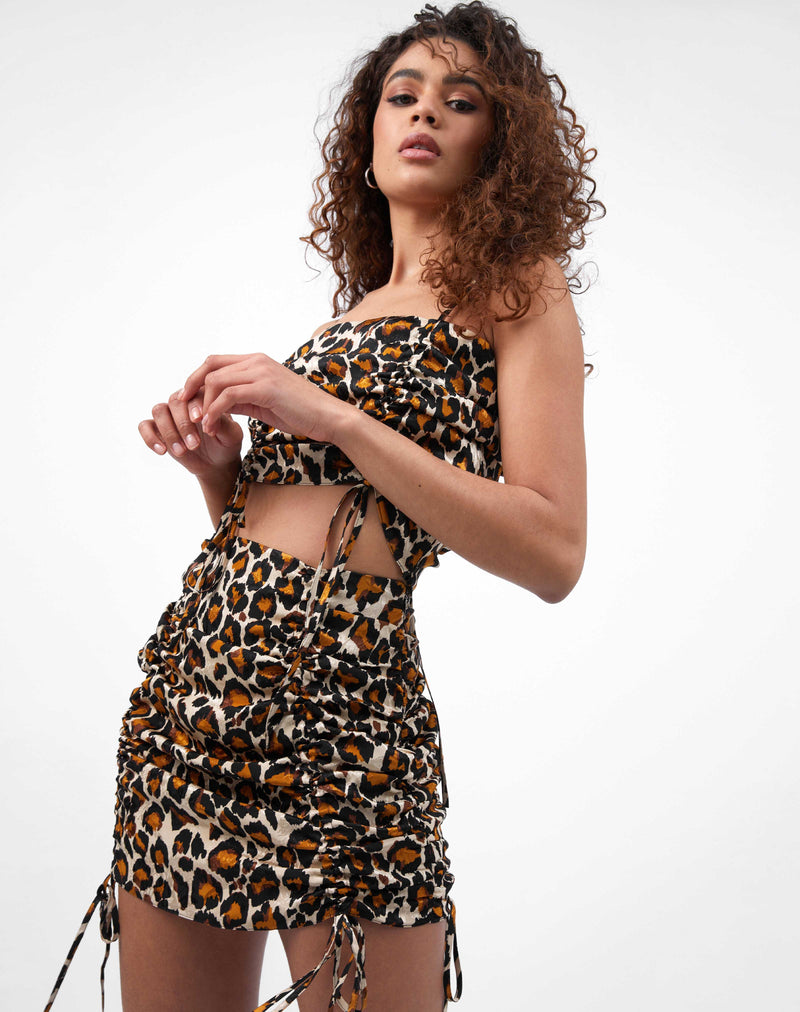 the model wears the dani leopard print ruched front top with the matching skirt while looking at the camera with hands held in front of her