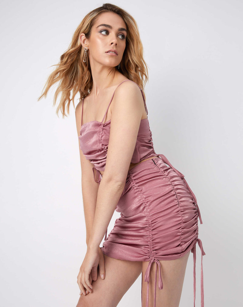 model leans on one side while wearing the dani pink ruched cami top in satin with matching noor skirt
