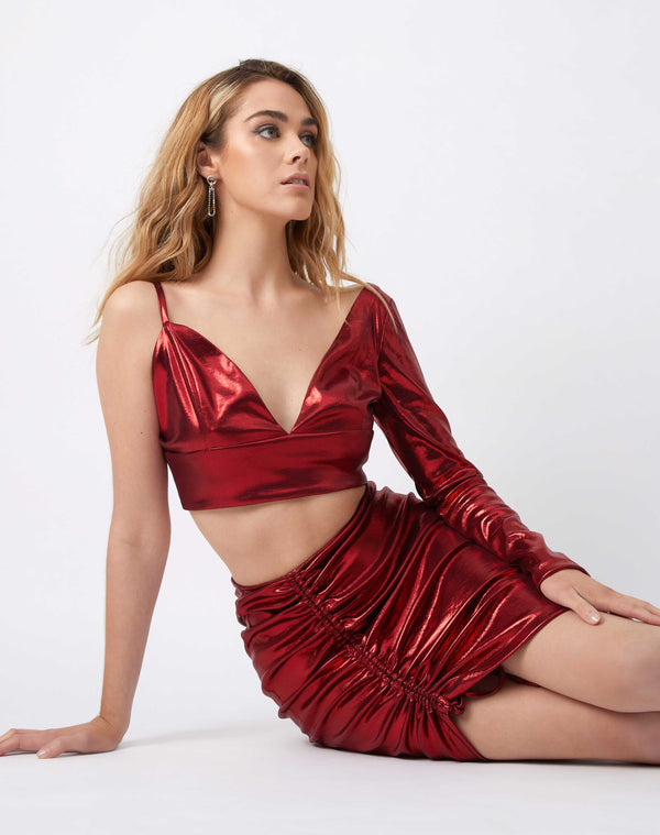 model wears the bella asymmetric red shimmer crop top with one strap and one long sleeve while sitting on the floor with the matching skirt
