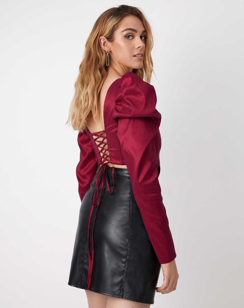 model shows the lace up back of the Rosie Pink Corset Style Top looking over her shoulder with a pu skirt