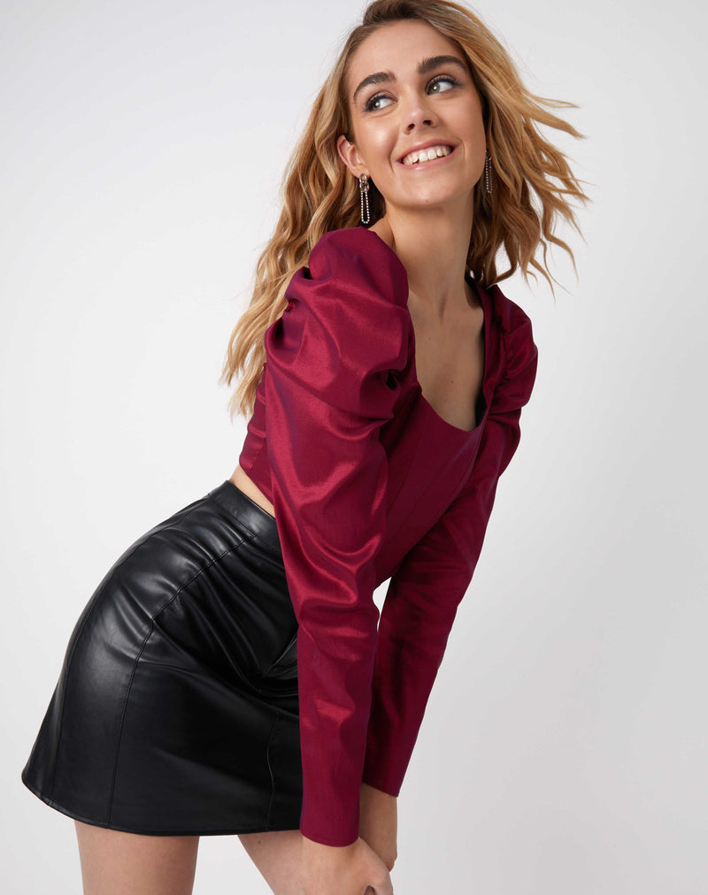 model leans on one leg and smiles wearing the Rosie Pink Corset Style Top and pu skirt