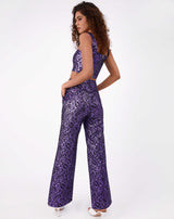 model has hands on hips with back towards the camera wearing the holly purple glitter jacquard trouser with matching top