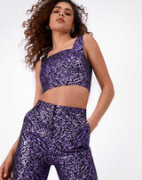 image shot from below of model wearing co-ord set with holly purple glitter jacquard trousers