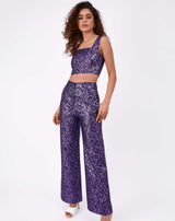 full length image of model in holly purple glitter jacquard wide leg trousers and matching crop top in white heels