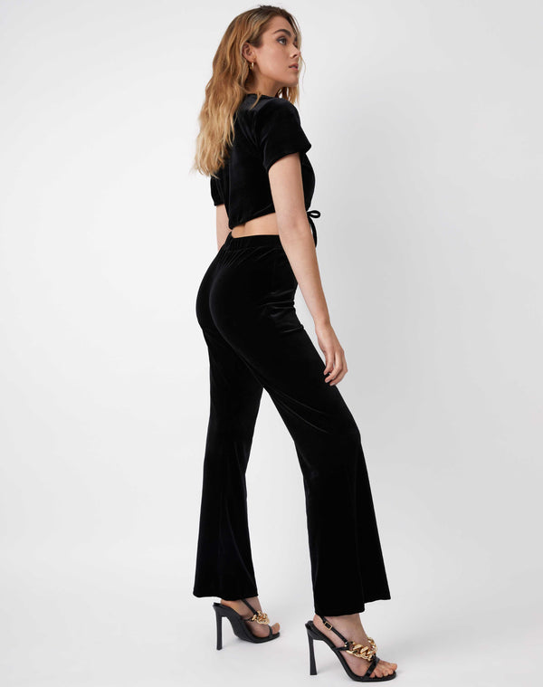 model looks over her shoulder while wearing brudget black velvet wide leg trousers from the back with matching top and black heels