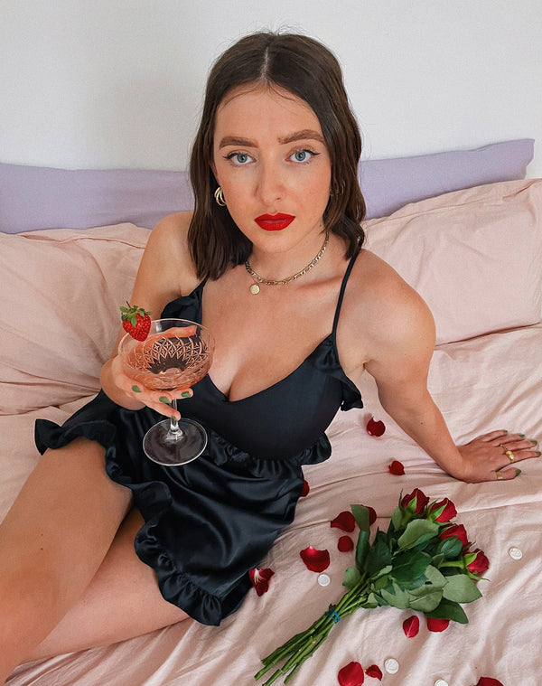model sits on a bed in the vanessa black satin frill night dress holding a glass of champagne next to roses and rose petals