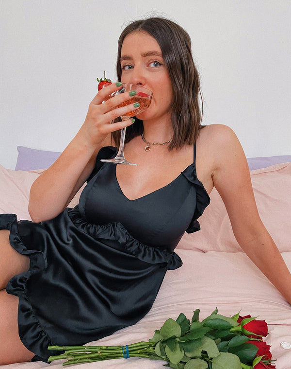 model sits on a bed wearing the vanessa black satin frill night dress while sipping champagne