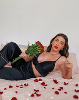 model leans back on a bed wearing the vicky black satin frill bralette with matching trousers while holding a bunch of roses