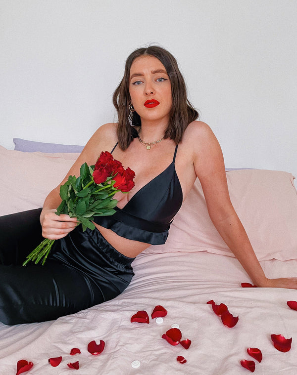model leans on her arm while sitting on a bed wearing the vicky black satin frill bralette with matching trousers while holding a bunch of roses
