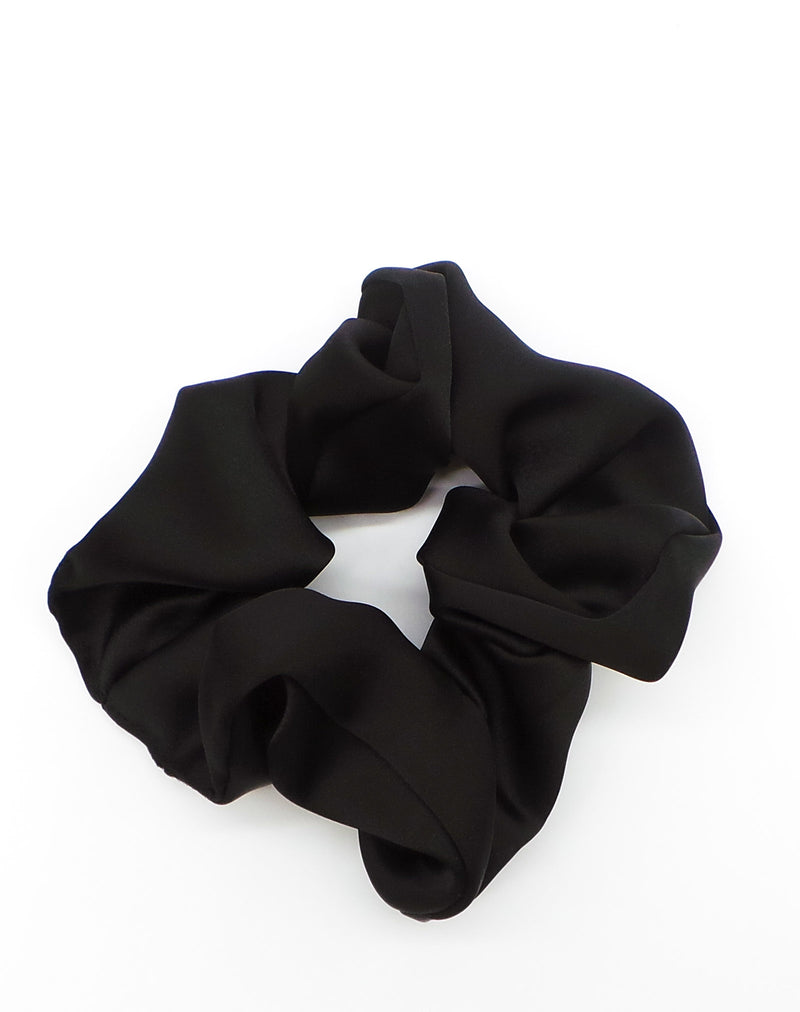 a close up image of a black hair scrunchie on a white background
