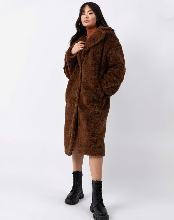 full length picture of model wearing buttoned up gigi brown longline teddy coat with chunky boots