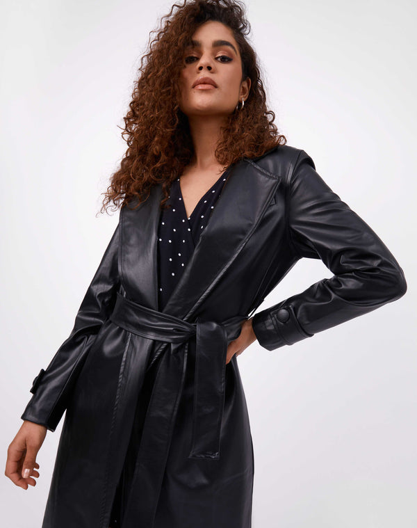 model has the coco faux leather coat on with belt tied over a polka dot dress