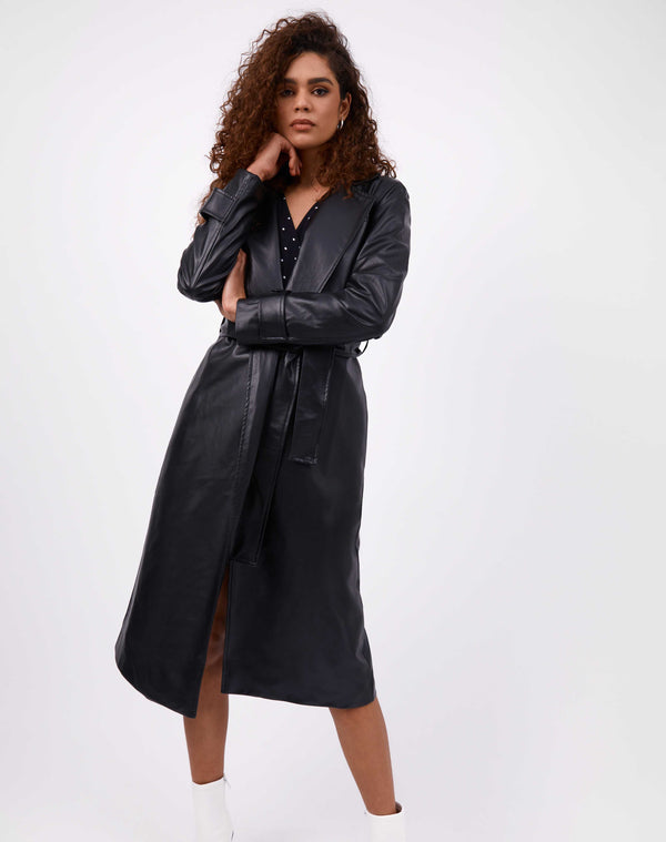 model wears the coco faux leather trench coat over a polka dot dress in front of a white background