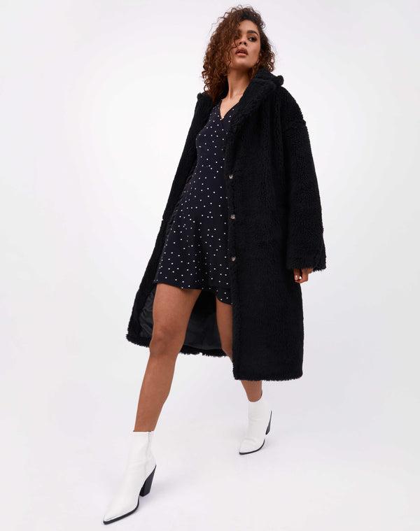 model walks towards camera wearing the gigi black teddy longline coat over polka dot dress with white boots