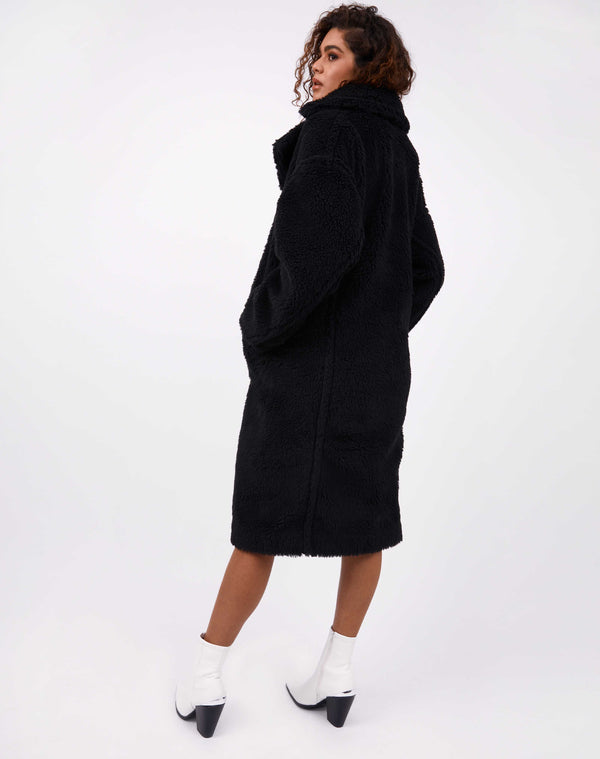 model faces away from the camera in gigi black teddy longline coat with white boots