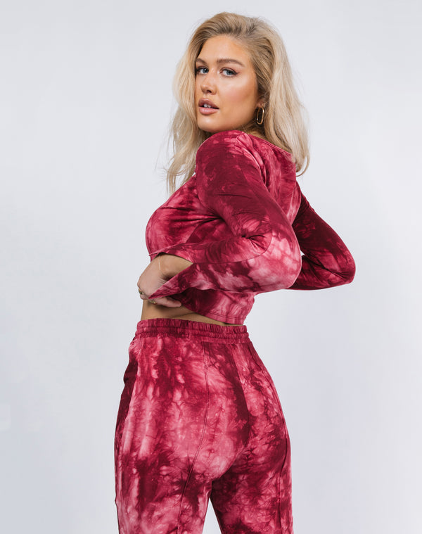 model turns away from the camera holding the hem of the Reign Red Tie Dye Cut Out Top with matching trousers
