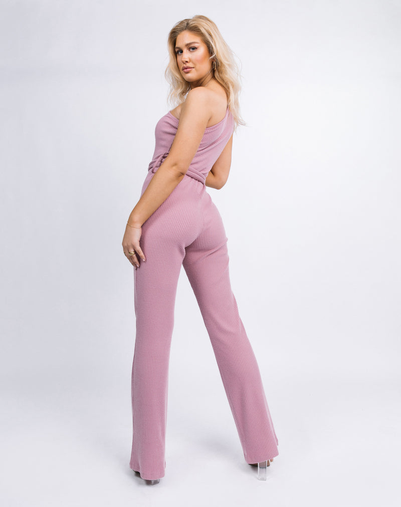 model looks over her shoulder while wearing the Laura One Shoulder Jumpsuit in Ribbed Blush
