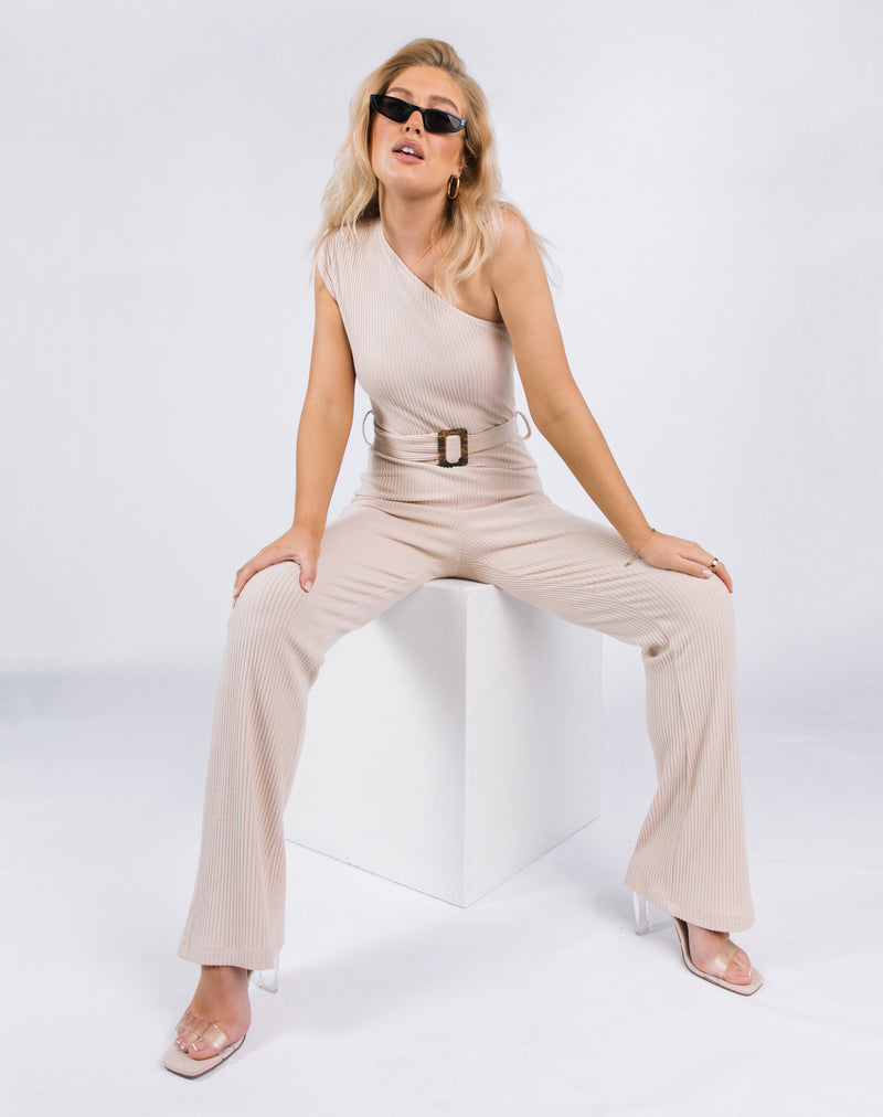 model sits on a block wearing the Laura One Shoulder Jumpsuit in Ribbed Oyster with sunglasses and perspex heels