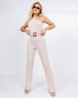 model stands with her hands on her hips wearing Laura One Shoulder Jumpsuit in Ribbed Oyster