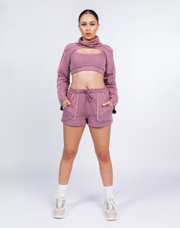 model is wearing the Michelle Contrast Pocket Shorts in blush with matching just sleeves and crop top with trainers