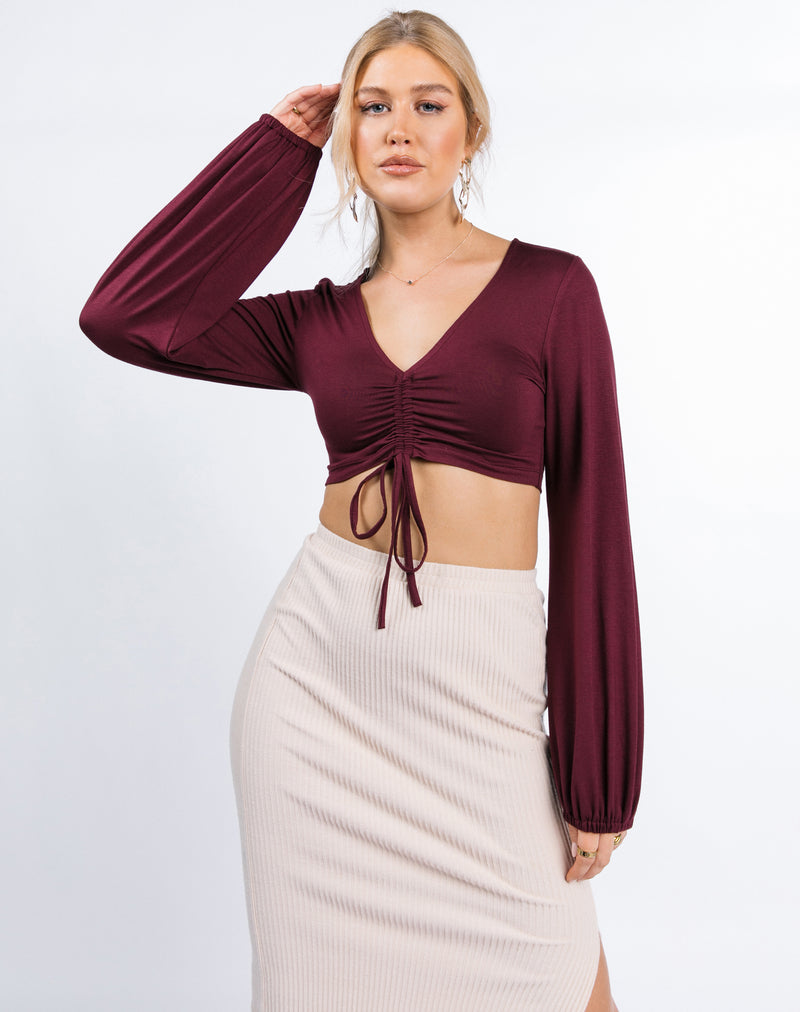 model holds one hand to her head in the Skye Ruched Front Crop Top in Grape with nude skirt