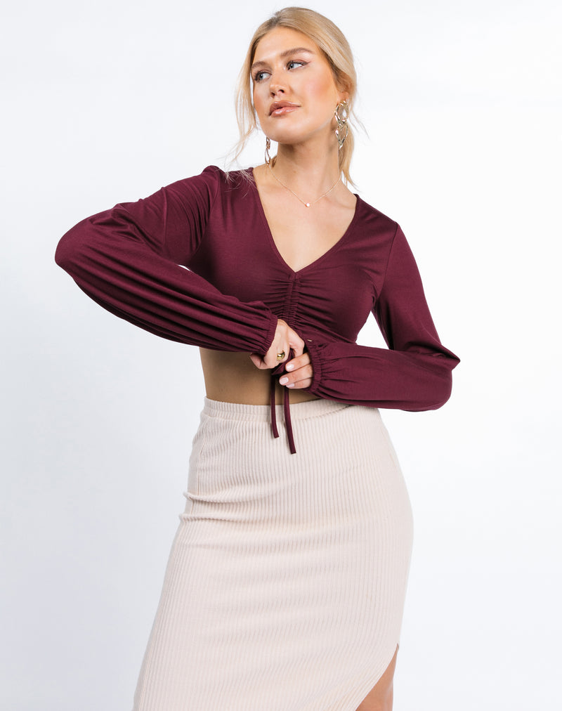 the model is holding her hands in front of her while wearing the Skye Ruched Front Crop Top in Grape with nude ribbed skirt