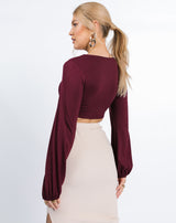 model faces away from the camera showing the back of the Skye Ruched Front Crop Top in Grape