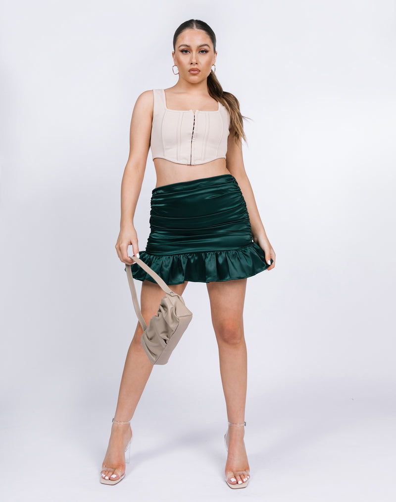 model stands towards the camera in the lucy green satin ruched skirt with beige corset and ruched bag