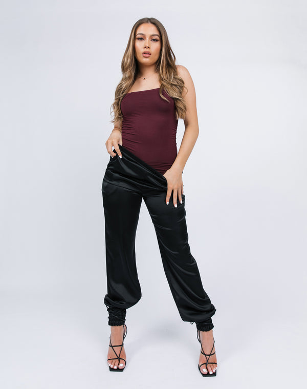 model wears the kyla black satin joggers with a red bodysuit and black tie up heels