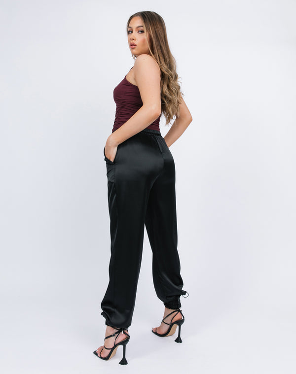 model wears the kyla black satin joggers with a red bodysuit and black tie up heels showing us the back